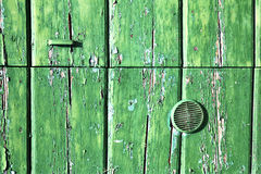 Green  knocker in a   closed wood door  lonate ceppino   italy Royalty Free Stock Photos
