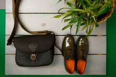 Green lacquered oxford shoes and crossbody bag on wooden background near flower pot. Top view. Close up. Copy space Royalty Free Stock Photos
