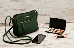 Green ladies handbag, phone, eyeshadow palette and a lipstick on a wooden background Stock Photo