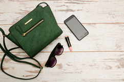 Green ladies handbag, sunglasses, phone and lipstick on wooden background. Fashionable concept. Top view Royalty Free Stock Image