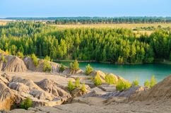 Green lake between forest and mountains. Green lake between forest and rocky lakeshore Stock Photography