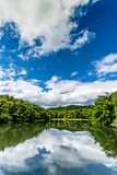 Green lake with green tropical forest and white cloud on blue sk stock photography