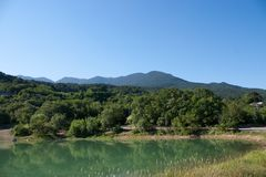Green lake in the mountains. Near the green hills stock photo