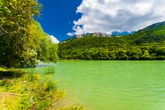 Green lake rippling close to mountains. Sunny landscape. Beautiful reservoir near hills stock image