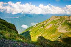 Green land landscape mountains valley in summer afternoon with gentle clouds over peaks stock photo