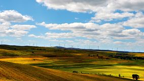 Green land and windmill array, China. The windmills on colorful hill generating clean energy. Panoramic view of healthy environment royalty free stock photography