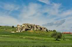 Green landscape with a beautiful rock formation. Under blue skies with fluffy white clouds Stock Photo