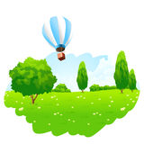 Green Landscape with Hot Air Balloon in the Sky Stock Photo