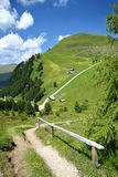 Green landscape with mountain huts viewed from a hiking path leading to Mount Pic above Raiser Pass, Val Gardena royalty free stock photos