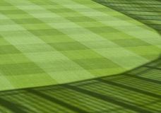 Green, landscaped grass of sports field with fence shadow Royalty Free Stock Image