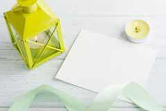 Green lantern with lit candle. And empty note over white wooden background. Copy space for text Royalty Free Stock Image