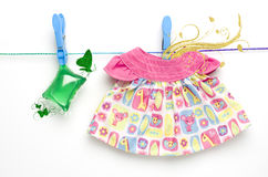 Green laundry gel capsules and dress hanging on washing line on white background Royalty Free Stock Image