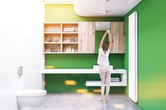Green lavatory interior, cabinets, woman. White and green lavatory interior with a concrete floor, a double sink, cabinets and a toilet. Woman 3d rendering mock Stock Photo