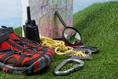 On a green lawn background, a set of items to search for, tourists, difficult situations, map, walkie-talkie and prepared. Red shoes stock photo