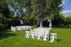 Green lawn with chairs for a ceremony. White decorated chairs on a green lawn. Chairs set in rows for wedding ceremony. They are decorated for festive event Stock Photo