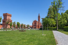 Green lawn, church and medieval tower in Pollenzo, Italy. Royalty Free Stock Photos