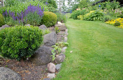 Green lawn and flowerbeds Stock Images