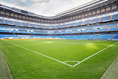 Green lawn with marking at empty outdoor football stadium. With blue seats and lighting system for growing grass Royalty Free Stock Images