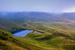 On the green lawn at the mountains there is a small lake. Royalty Free Stock Photography