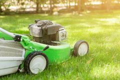 Green lawn-mower on fresh lawn at yard. Tools for cutting grass. Gardening and equipment service concept.  Royalty Free Stock Image