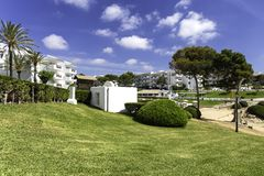 Green lawn, palms and trees near the hotels in Mallorca, Spain royalty free stock photography