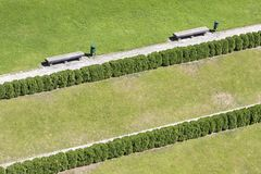 Green lawn with park bench, hedge and garbage basket. In Poland Stock Photos