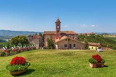 Green lawn and red church in Piedmont, Italy. Royalty Free Stock Image