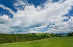 Green lawn on rural landscape with clouds on sky Royalty Free Stock Image