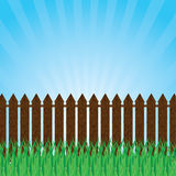 A green lawn with shrubs and trees and fence . Stock Photography