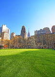 Green Lawn and Skyline with Skyscrapers viewed from Bryant Park. In Midtown Manhattan, New York, USA. Tourists relaxing in the park Royalty Free Stock Images