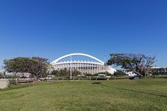 Green Lawn and Trees against Moses Mabhida Stadium. DURBAN, SOUTH AFRICA - FEBRUARY 23, 2018: Morning view of empty green lawn and trees against Moses Mabhida Royalty Free Stock Photos