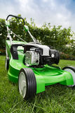 Green lawnmower on green lawn. Royalty Free Stock Photo