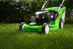 Green lawnmower on green lawn Royalty Free Stock Photos
