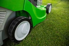 Green lawnmower on green lawn Royalty Free Stock Images