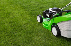 Green lawnmower on green lawn. Outdoor shot of green lawnmower Royalty Free Stock Photos