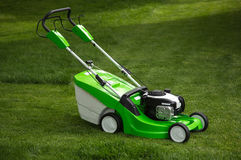 Green lawnmower on green lawn Royalty Free Stock Photo