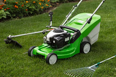 Green lawnmower, weed trimmer, rake and secateurs in the garden Royalty Free Stock Photography