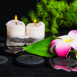 Green leaf calla lily, plumeria with drops and candles on zen st Stock Image
