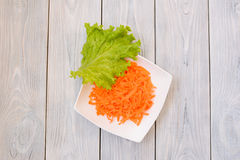 Green Leaf on Carrot Plate. Green salad leaf on plate with carrot. flat lay. top view Stock Photography