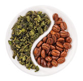 Green leaf tea versus coffee beans in Yin Yang. Shaped plate, isolated on white stock photography