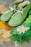 Green leather boots, scarf and yellow leaves Royalty Free Stock Image