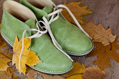 Green leather boots and yellow leaves Royalty Free Stock Photo