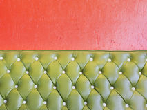 Green leather of vintage luxury armchair and orange wall Royalty Free Stock Photos