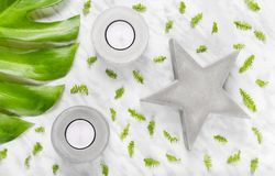 Green leaves and concrete decorations on marble background. Green leaves, concrete star and candle holders on marble background. Flat lay composition stock images