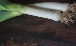 Green leek on a rustic table. Green leek on a wooden table , Horizontal composition, with a space for text. Selective focus Stock Photography