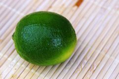 Green lemon on bamboo. Single green l on bamboo zoomed Stock Photo