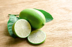 Green lemon and a half on wood background Stock Images