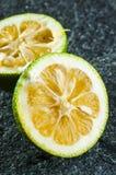 Green lemon halves. Two green lemon halves close up on gray stone background stock photography