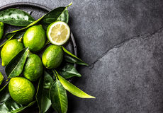 Green lemon Lime with fresh leaves on black plate, slate background royalty free stock photos