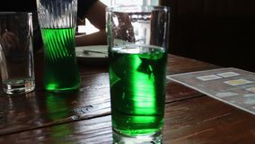Green lemonade bubbles in glass on a table in a cafe stock footage